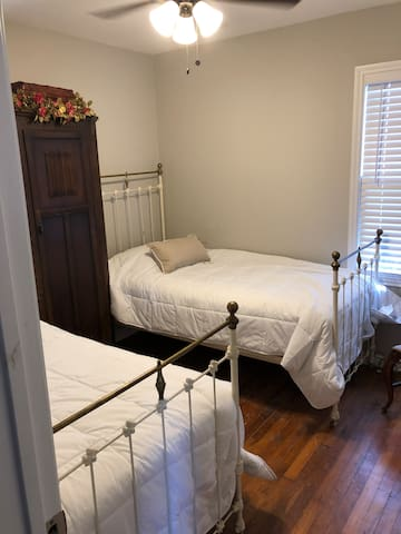 The second bedroom has two vintage twin beds and easy shared access to the bathroom with a subway tile shower!