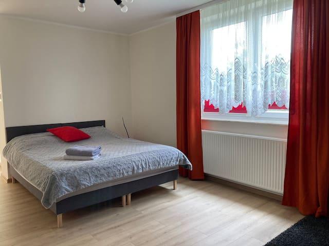 Pokój CZERWONY. Pokój znajduje się na 2 poziomie i jest z balkonem Łóżko 160x200 cm Rozkładana kanapa 120x200 cm. Kanapa rozkłada się do poziomu podłogi i jest idealna dla dzieci. Łóżeczko niemowlęce. Pokój wyposażony jest w tv, stolik, fotel i regał