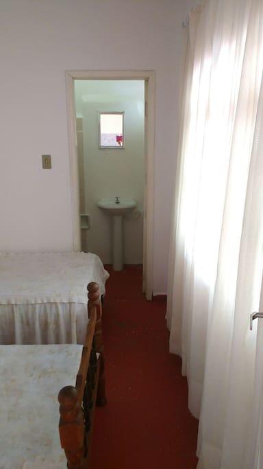 Quarto arejado com banheiro.