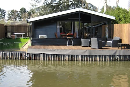 Modern chalet in a small park, located right along a fishing pond