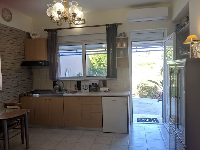Kitchen area with all appliances, dining table, cupboards, window and air-conditioning