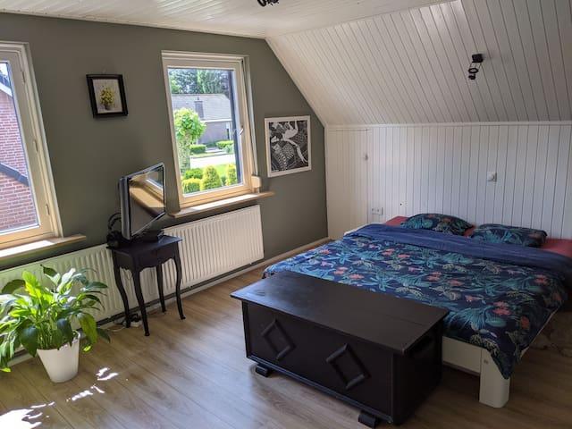 Ruime slaapkamer op 1e verdieping met rolluiken en horren voor de ramen