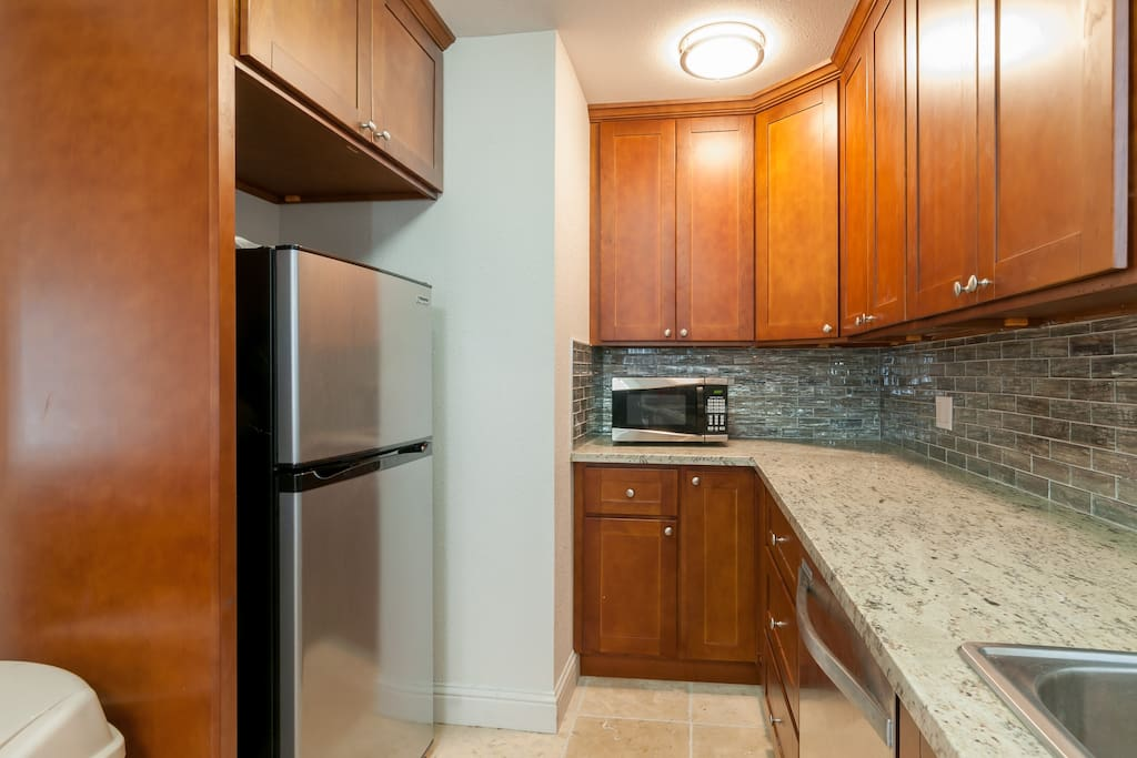 View of refrigerator, microwave and plenty of counter top space.