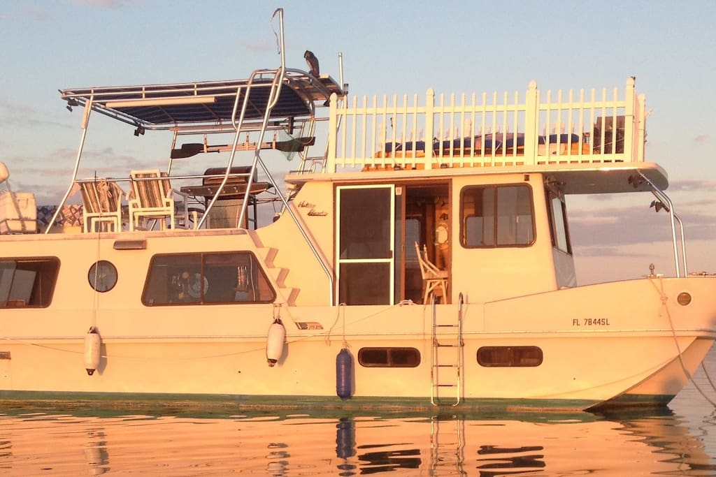 Houseboat has white picket fence on upper roof and custom tee top