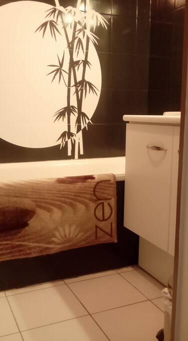 Salle de bain avec baignoire , sèche cheveux , serviettes