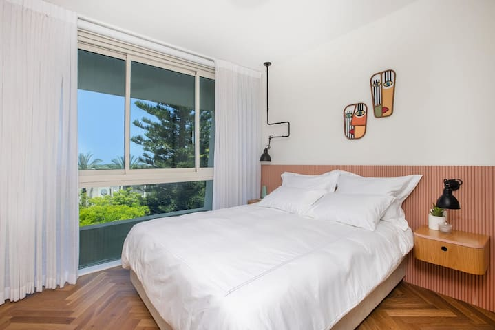 חדר שינה עם מיטת קינג סייז,  עם וילון חשמלי ונוף לים