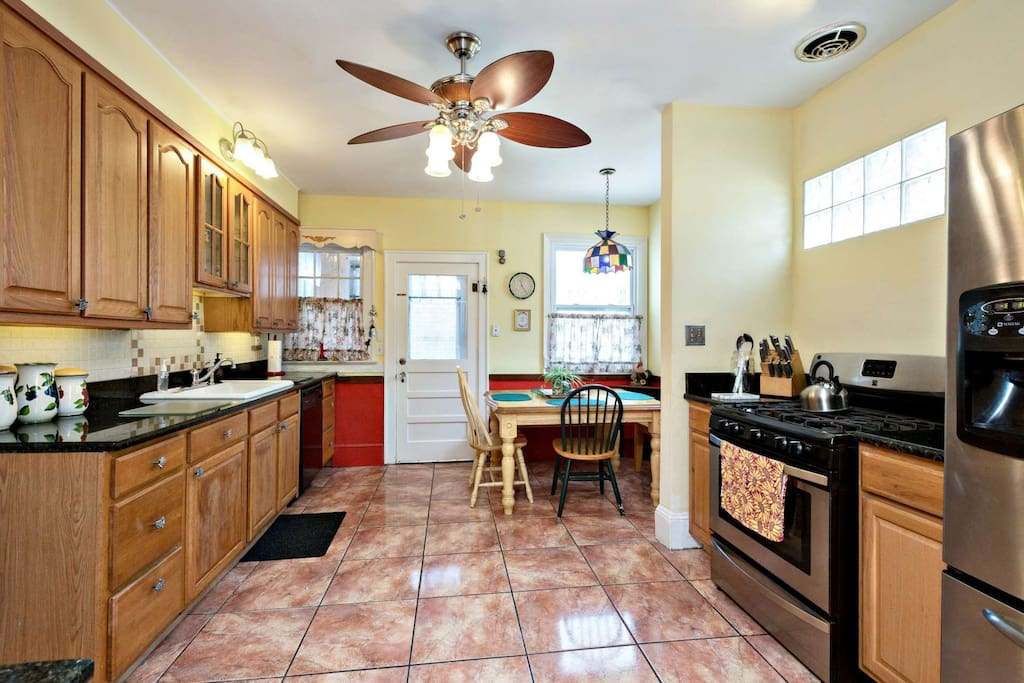 Modern kitchen with refrigerator, stove/oven, dishwasher, microwave, toaster, coffee pot, tea kettle and ceiling fan.