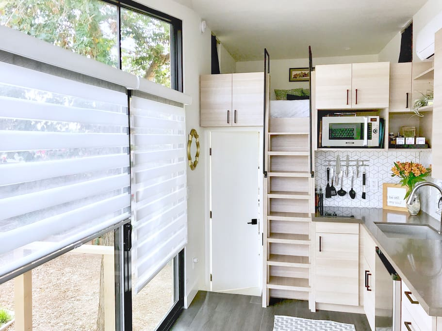 Large, deep sink, undercounter fridge, 2 burner cooktop, convection microwave (with baking capabilities), and HVAC system.