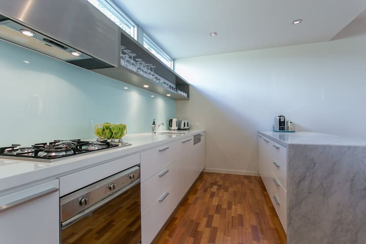 Beautiful kitchen with marble floating bench inc Microwave, dishwasher and coffee machine