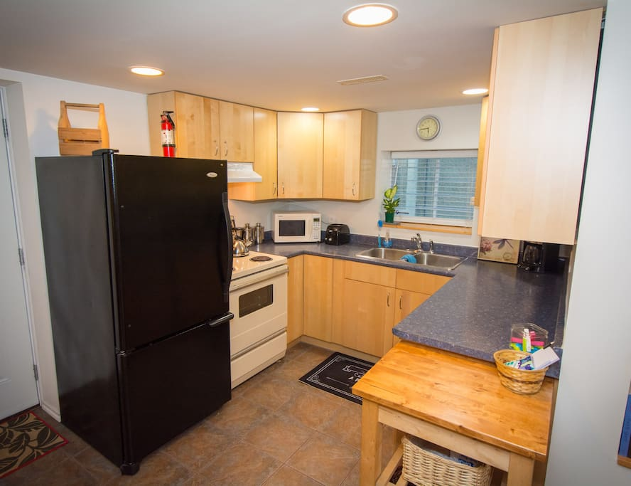 Kitchen with fridge, stove, microwave, toaster and coffee maker