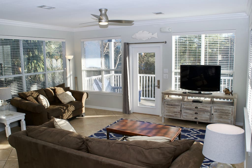 Bright and Spacious Living Area with Plenty of Seating and Large Screen TV