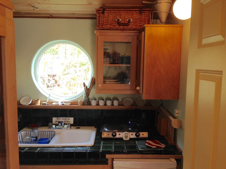 Kitchen with small fridge, hotplate, toaster oven, pots & pans, dishes, glasses, silverware, etc.