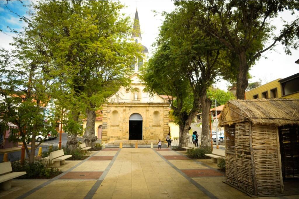La place  du Bourg de Sainte-Anne avec son église classée et une la réplique d'une case d'antan