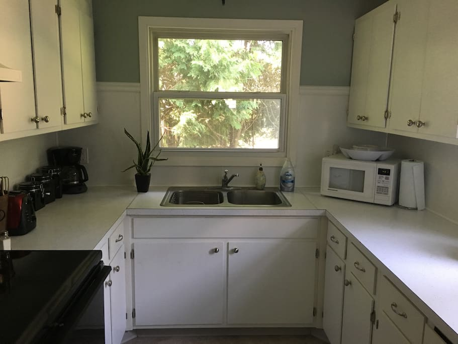 Full kitchen with electric range. Dishes and glassware