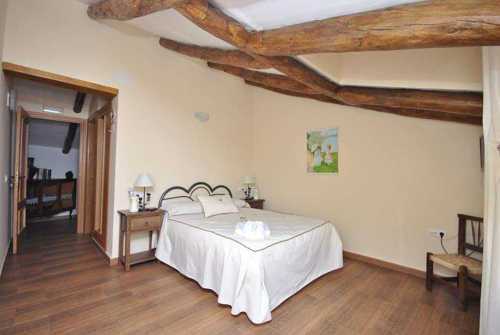 Dormitorio con tele y baño