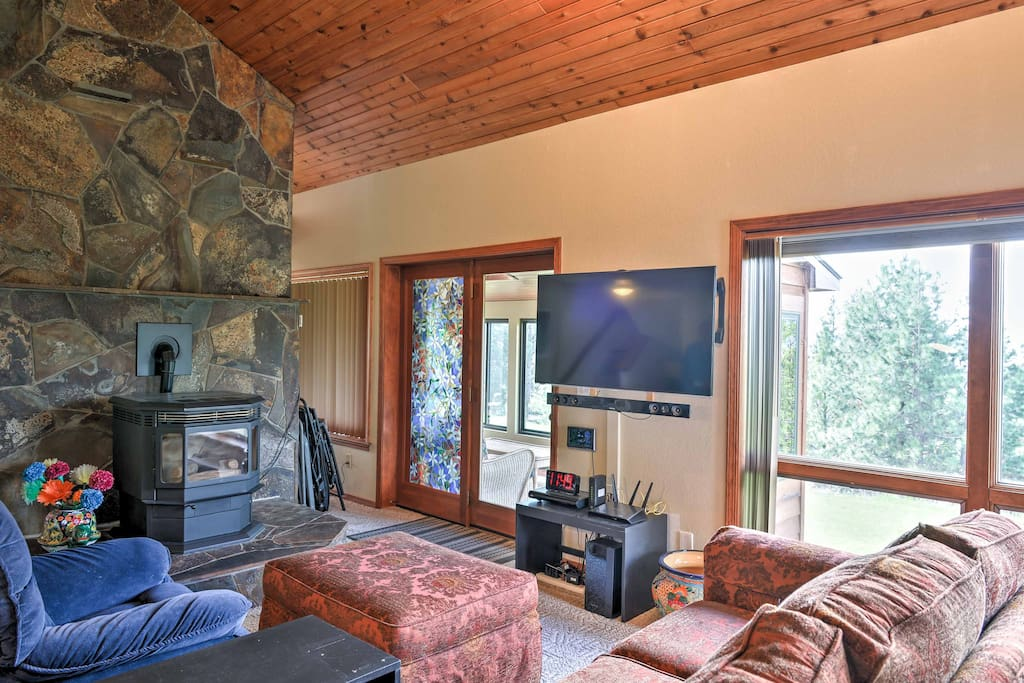 The living room offers plush seating, a wood-burning fireplace, a flat-screen cable TV, and an exercise machine.