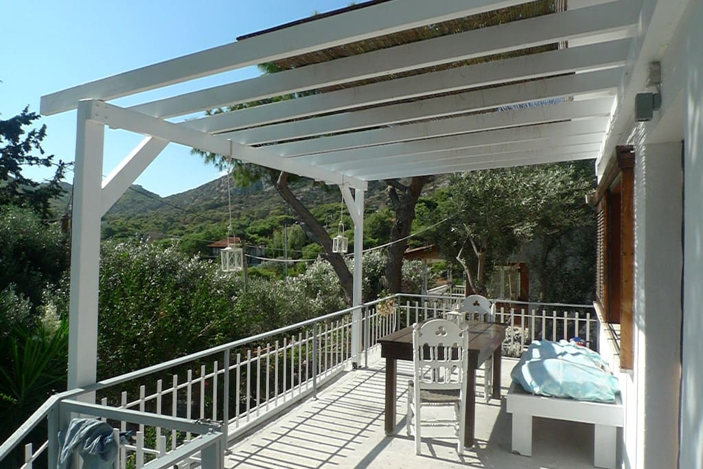 front balcony island style with pergola and bamboo olive trees are all around this summer setting quit in nature you can enjoy a relaxing breakfast or a lunch after swim.