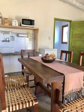 Estar con kitchenette equipada. Sofá y mesa para 6. Utensilios de cocina y vajilla