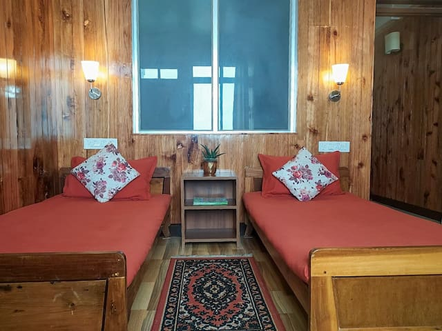 This bedroom has a unique feel of a cabin in the Himalayas. It is tastefully done & the wooden panelling adds warmth to the space. The room comes with a private patio/balcony.