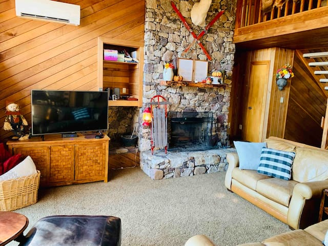 Living room. Large common space for football watching, or sit in-front of the stone fireplace with friends. It allows for groups to be able to spend time together.
