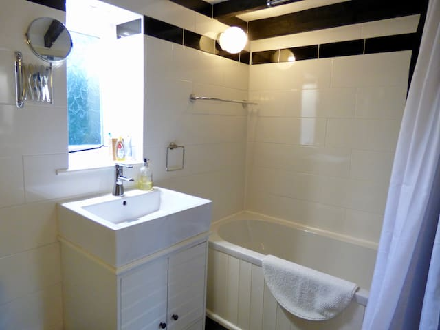 The main bathroom is modern and bright, with a 'proper-sized' bath and shower.