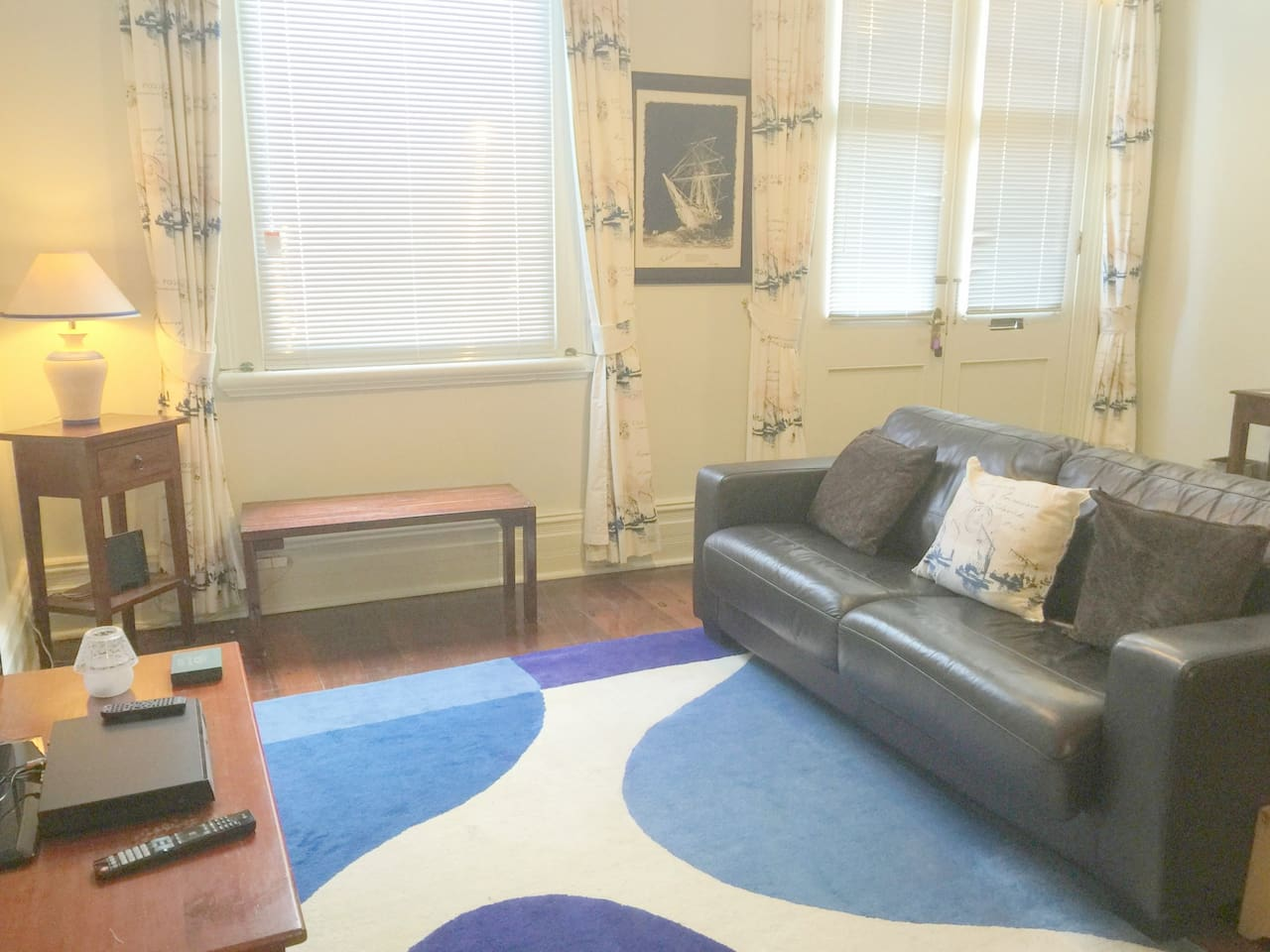 Sitting room on the ground floor with large comfortable leather sofa bed. Large TV and DVD player