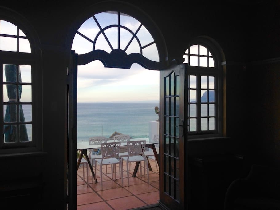 View from the lounge past the dining table on the balcony, to the sea.