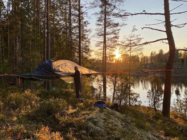 Trädtält i vildmarken med strand och kanot