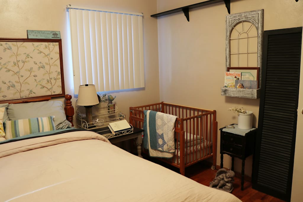 Guest bedroom with small crib. There is also a small chair and a closet.