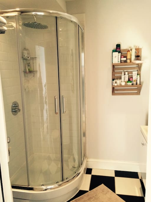A large shower with a monsoon shower head