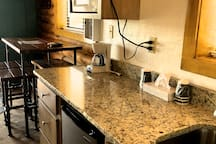 Kitchenette with mini fridge, micro wave, coffee maker, basic utensils, cups and tissue paper.