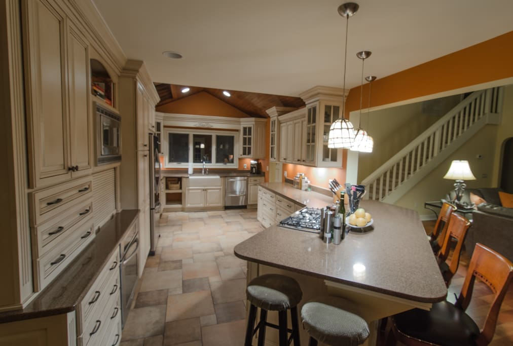 A large kitchen with a counter bar makes for a nice transition between the kitchen and living room.