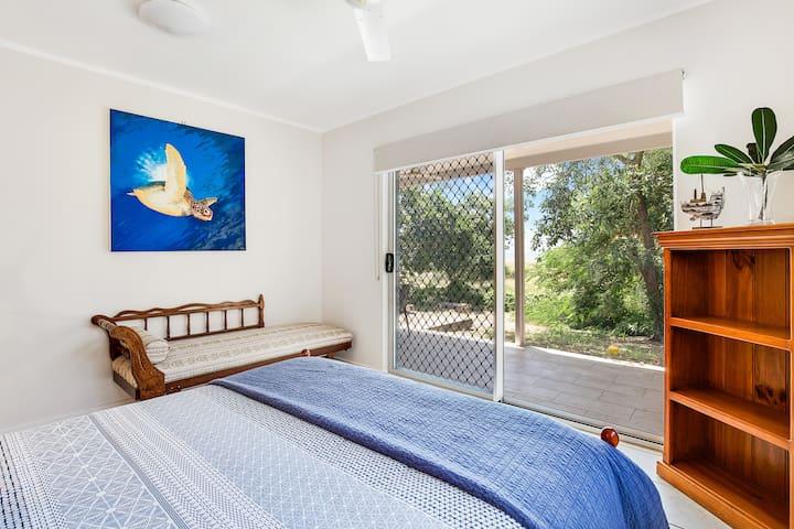 The beachfront master bedroom opening to the veranda