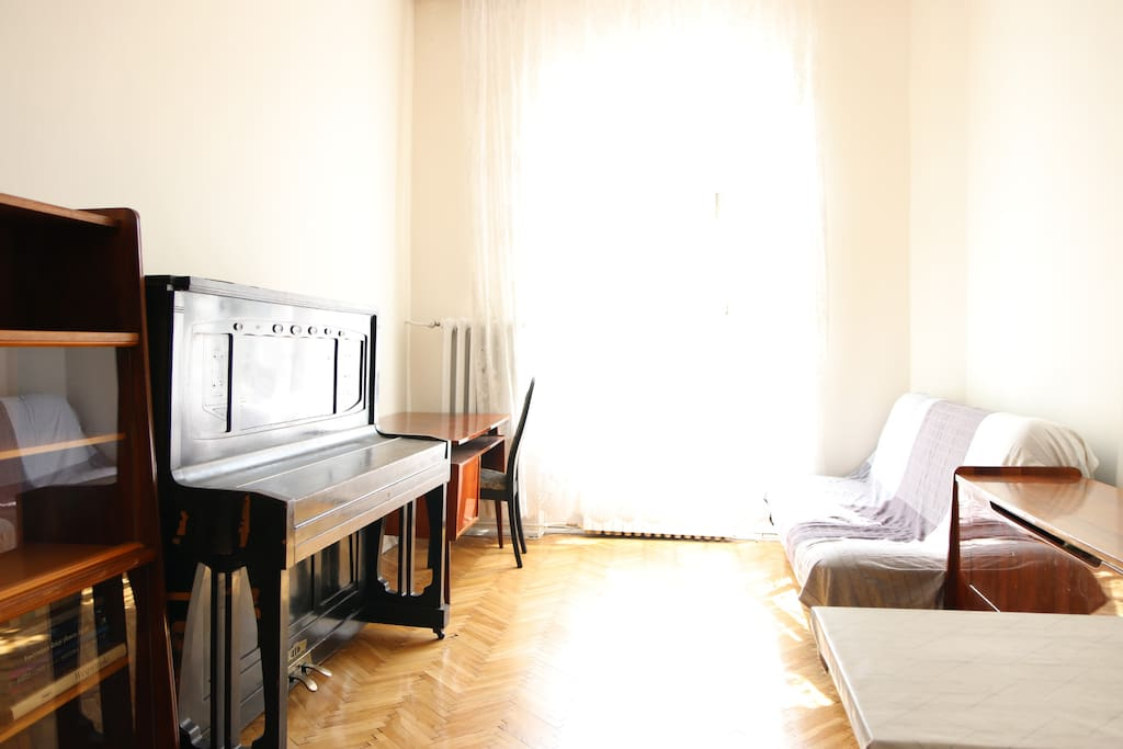 Living room - with piano, working desk, dining table and a sofa which can sleep two adults or children.
