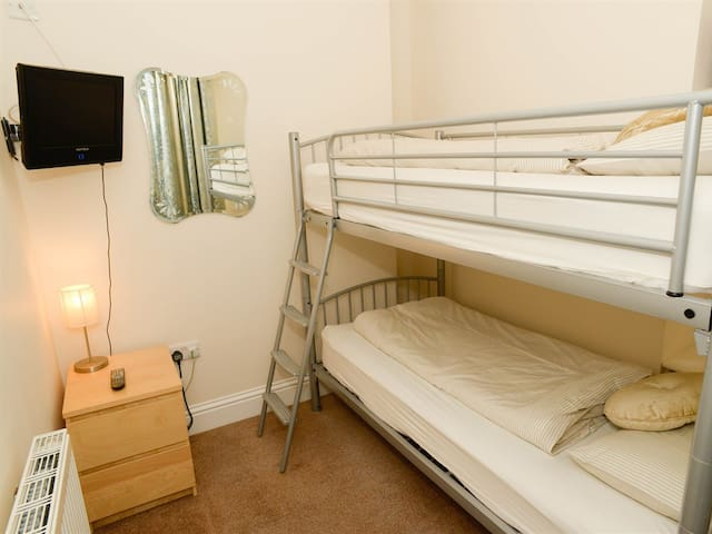 adjoining family room, full sized bunk beds, with own TV WIFI and sea view.