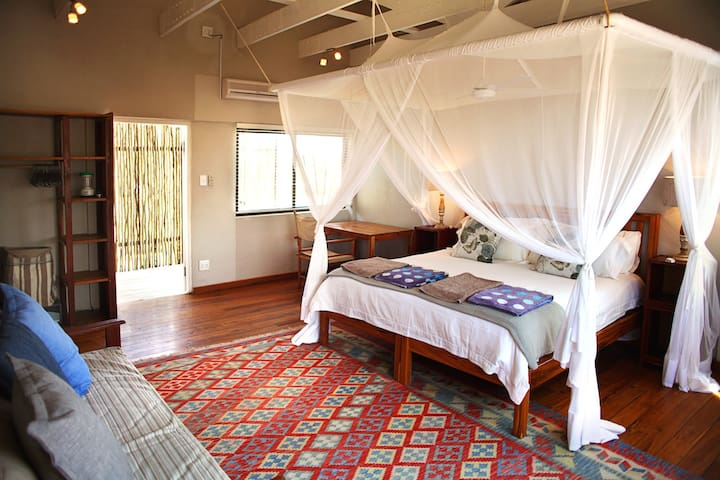 Spacious master bedroom upstairs, with a beautiful view down the beach.