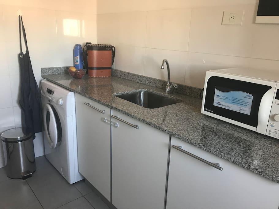 La cocina además cuenta con en espacio para el lavado que incluye lavarropas.