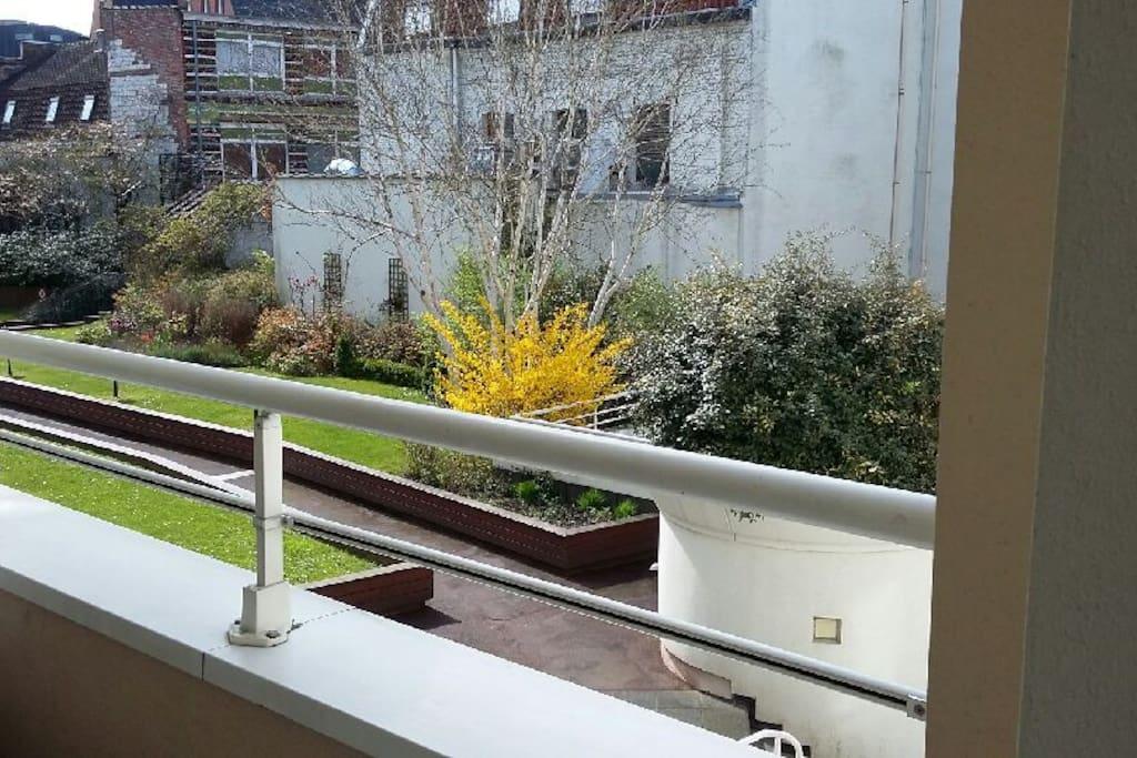 Balcon avec petite table et vue sur le parc privé de la résidence