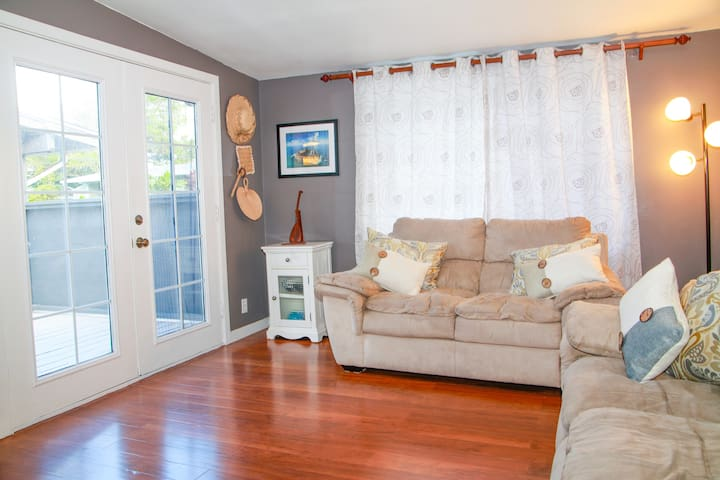 Relax after a day at the beach on our comfy sofas. French doors open out to a small lanai with more seating, hammock, and a nice table to eat at.