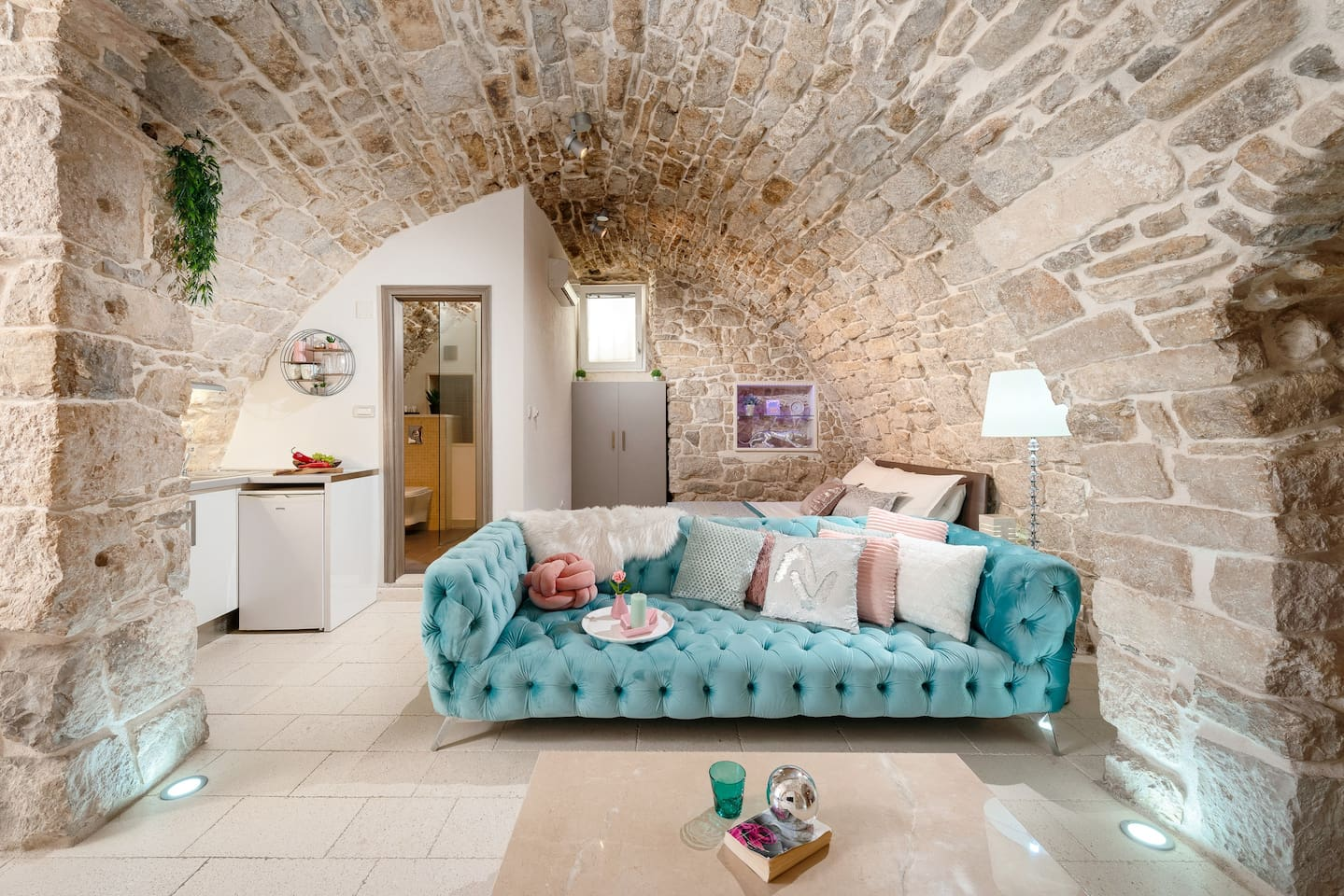 "The interior of the apartment is focused around sitting area.On the left side of the sofa there is a small but very charming kitchen.The door next to the kitchen leads to the""cave toalet"",and behind the sofa there is a most comfortable area- bed :)"