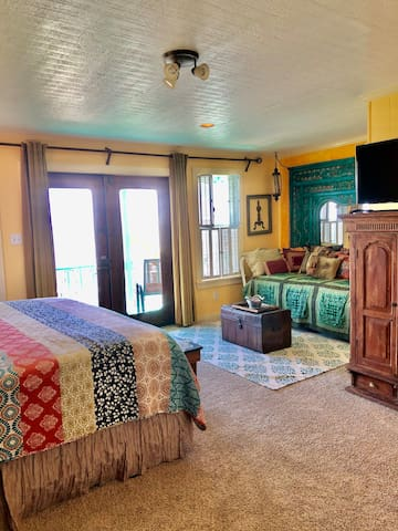 Overview of 3rd level en suite bedroom with hand-made doors leading to private waterfront balcony.  King size bed, twin size day bed, copper chest, tv & 2 unique wooden armoire's.  Private bathroom with tiled shower & bench and double copper sinks.