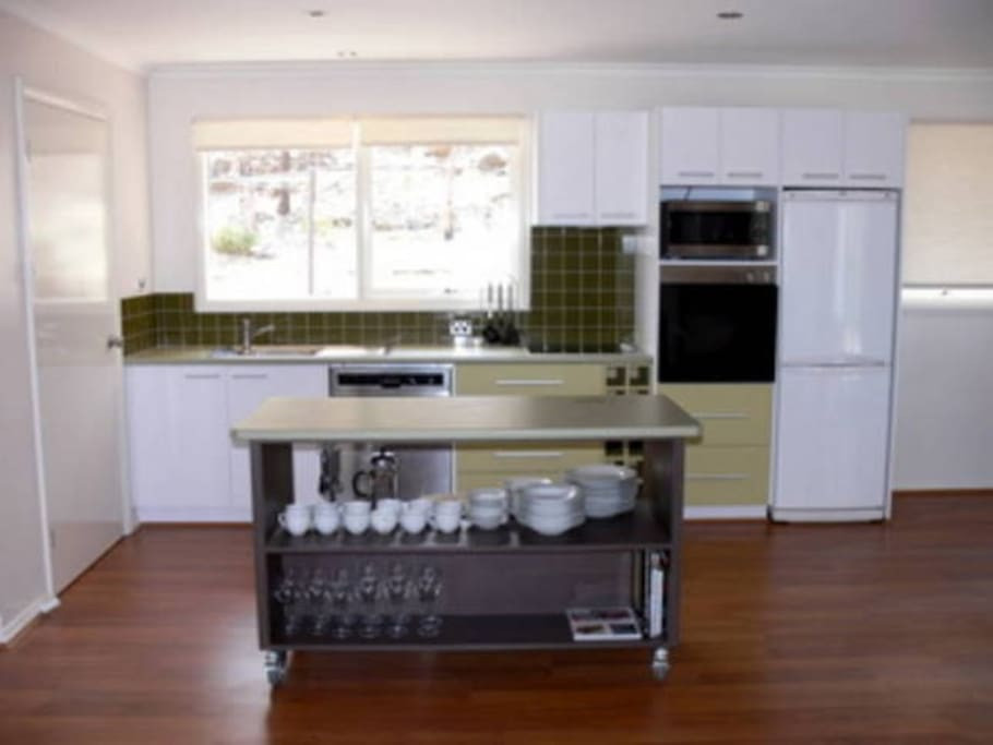 The kitchen contains modern appliances, walk-in pantry, wine rack, a variety of cookware, tools and cookbooks.