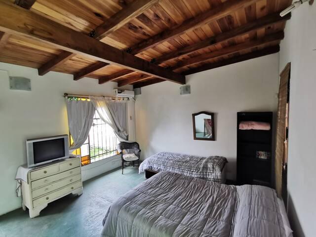 Gran dormitorio en planta alta de 5 x 5 m2, cama doble matrimonial y cama de una plaza, con televisión, wifi, aire acondicionado, y mucha iluminación natural.
