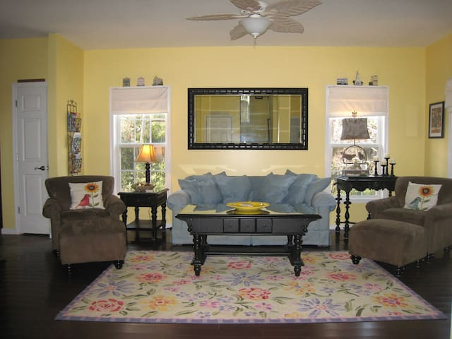 Living Room area with TV, walk onto charming front porch with  rockers.