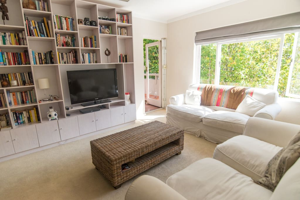 Spacious and sunny - our lounge area with comfy couches, a huge flat screen TV and all our books.