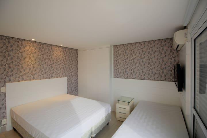 Suíte com uma cama queen, uma cama de solteiro e ar condicionado com vista para a Mata Atlântica.