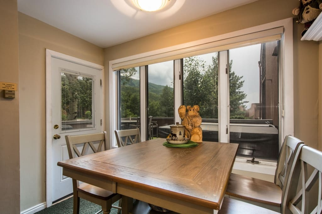 Adjacent to the living room is a traditional Park City dining room with large oversized windows, modern mountain furniture with seating for four (4).