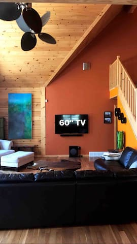 """Open concept living room with large sectional and 60"""" TV"""