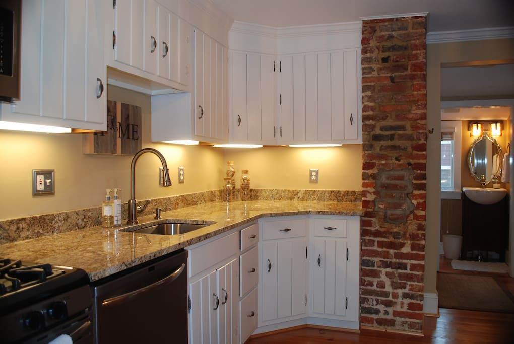 Well lit and appointed kitchen with exposed brick.