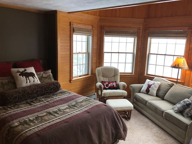 Second level - Bedroom #5 (sun room) overlooking the lake, featuring queen bed, dresser, sofa, and rocking chair.